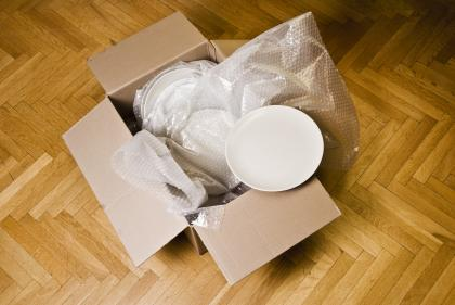 Box with dishes wrapped in packing materials