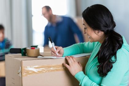 Woman preparing list and packing boxes for move.