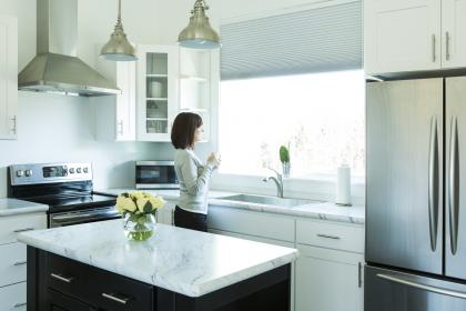 Woman standing in kitchen with new appliances