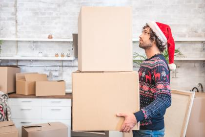 Man wearing Santa hat moving boxes on moving day